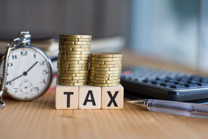 Close-up Of  the word Tax  On Wooden Blocks and a pocket watch and a calculator  on the background